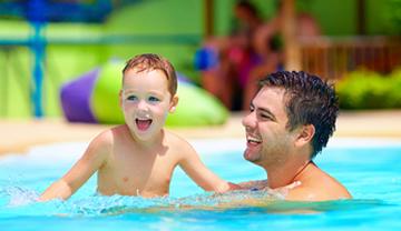 Dad and son enjoying their inground swimming pool