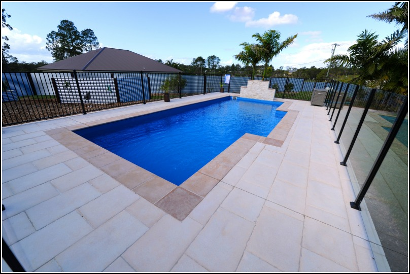 Heritage lap pool design idea. Photo displays fibreglass inground lap pool in a backyard pool setting with glass pool fencing and sandstone look pool pavers